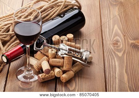 Glass of red wine, bottle and corkscrew on rustic wooden table with copy space