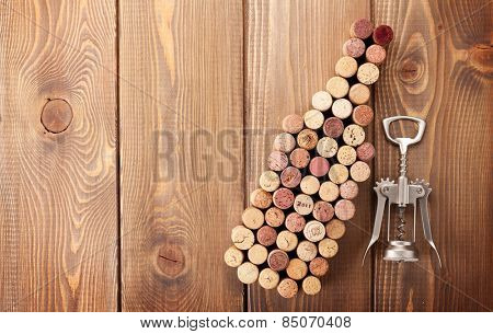 Wine bottle shaped corks and corkscrew over rustic wooden table background. Top view with copy space