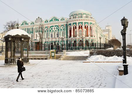 YEKATERINBURG, RUSSIA - JANUARY 1, 2015: Girl make photo of the house of N. I. Sevastianov. Built in the first quarter of XIX century, now it is one of the most notable landmark of the city