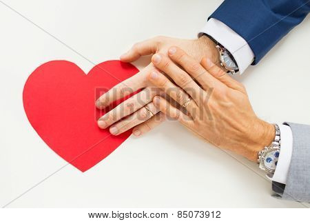 people, homosexuality, same-sex marriage, valentines day and love concept - close up of happy married male gay couple hands with red paper heart shape on table