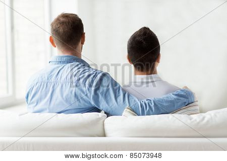 people, homosexuality, same-sex marriage, gay and love concept - close up of happy male gay couple or friends hugging from back at home
