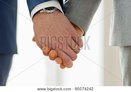 people, homosexuality, same-sex marriage and love concept - close up of happy male gay couple holding hands with wedding rings on