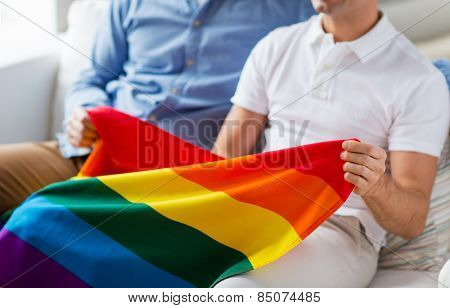 people, homosexuality, same-sex marriage, gay and love concept - close up of happy male gay couple hugging and holding rainbow flag at home