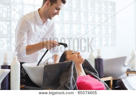 beauty and people concept - happy young woman with hairdresser washing head at hair salong