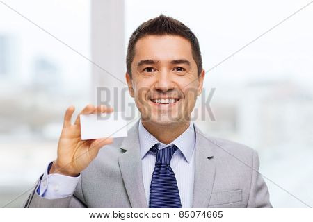 business, people and office concept - smiling businessman in suit showing blank white visiting card