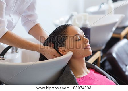 poster of beauty and people concept - happy young woman with hairdresser washing head at hair salon