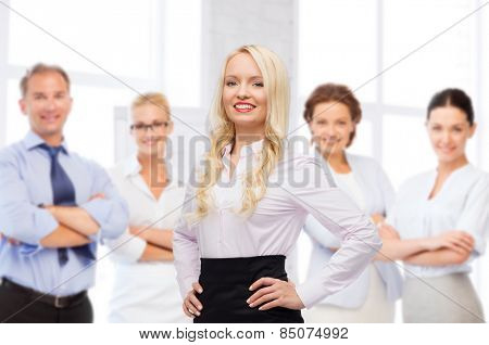 business, team work and people concept - smiling businesswoman, student or secretary over group of colleagues over office background