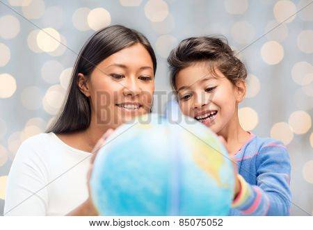 family, children, education, geography and people concept - happy mother and daughter with globe over holidays lights background
