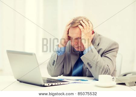 business, technologym communication and office concept - upset older businessman with laptop, charts, coffee and telephone in office