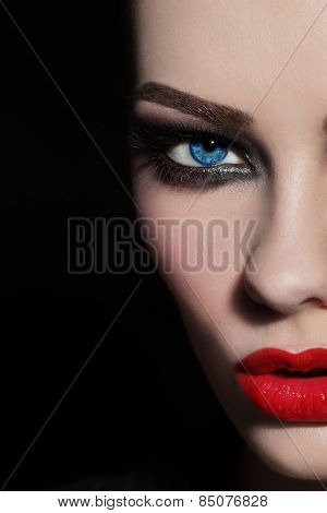 Close-up shot of woman's face with red lips and smoky eyes, selective focus