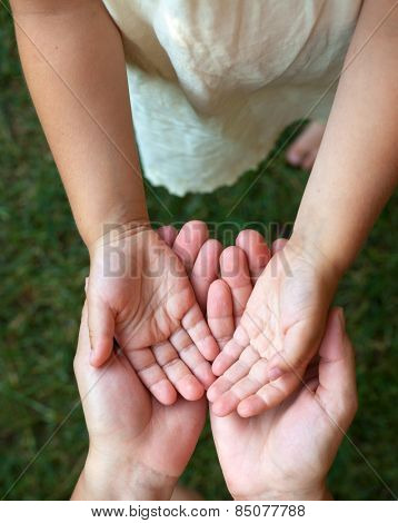 Little girl showing her hands to mother outdoors