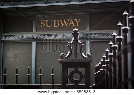 The word Subway painted in gold on the side of an antique rail station with black wrought iron fence in the foreground.