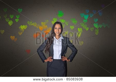 Smiling Young Businesswoman on Gray Gradient with Conceptual Colored Hearts Pattern Design.