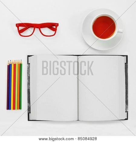 high-angle shot of a some colored pencils, a blank notebook, a pair of red plastic-rimmed eyeglasses and a cup of tea on a white table