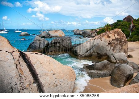 Close up Huge Granite Rocks at the Baths in Beautiful Virgin Gorda Island with Boats Sailing Afar Under Light Blue and White Sky.