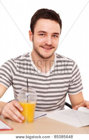 Young man sitting at the table with a pile of books.