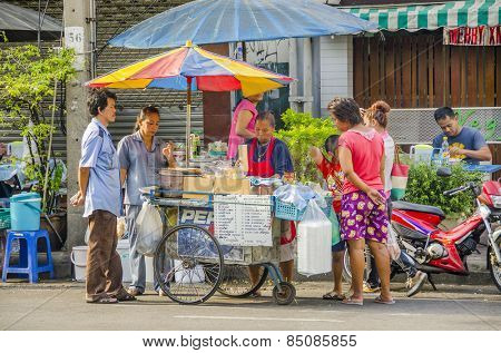 BANGKOK, THAILAND, DECEMBER 26, 2012: Local people buy food and drinks from street seller