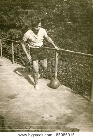 Vintage photo of teenager playing with a ball, 1960's