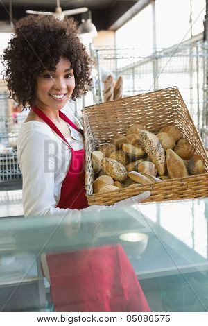 Pretty waitress carrying basket of bread at the bakery