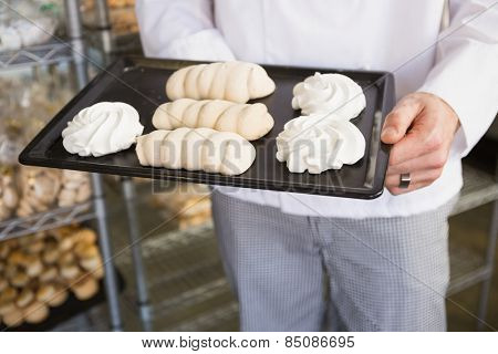 Mid section of baker holding meringue tray at the bakery