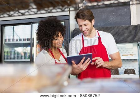 Colleagues in red apron using tablet at the bakery