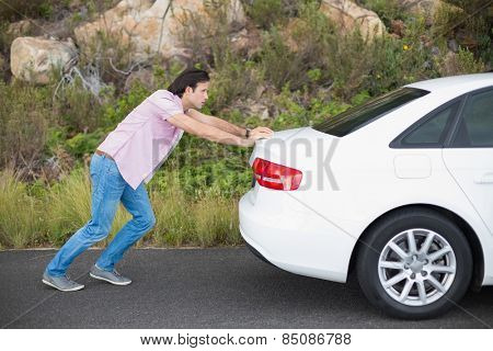 Man pushing car after a car breakdown at the side of the road