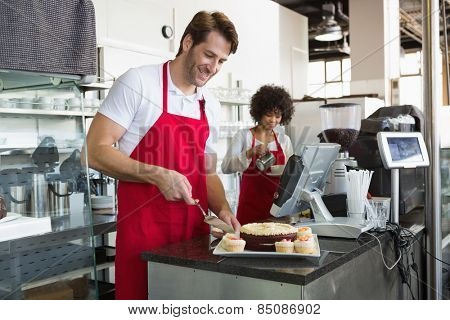 Smiling waiter slicing cake with waitress behind him at the bakery