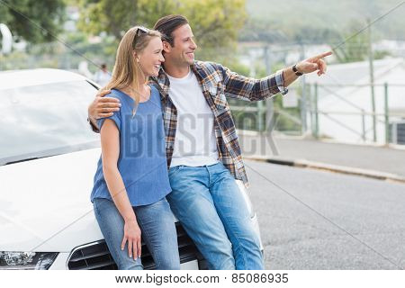 Smiling couple leaning on the bonnet of their car