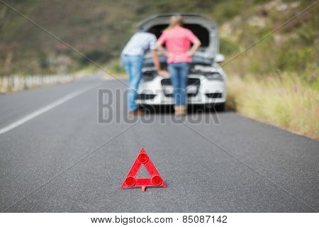 Young couple after a car breakdown at the side of the road