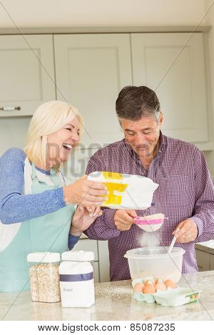Happy mature couple baking together at home in the kitchen