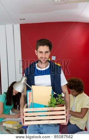 Portrait of handsome casual businessman carrying his belongings in box