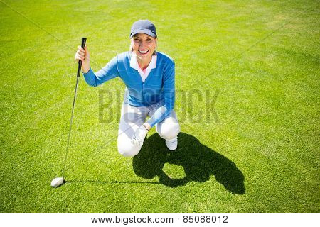 Smiling lady golfer kneeling on the putting green on a sunny day at the golf course