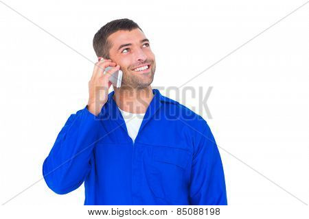 Happy mechanic looking up while talking on mobile phone over white background