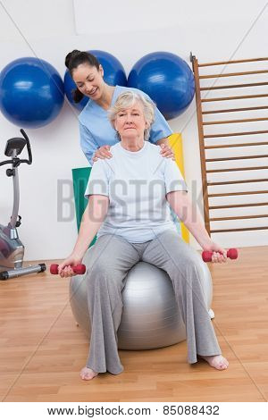 Therapist helping senior woman fit dumbbells on exercise ball in fitness studio