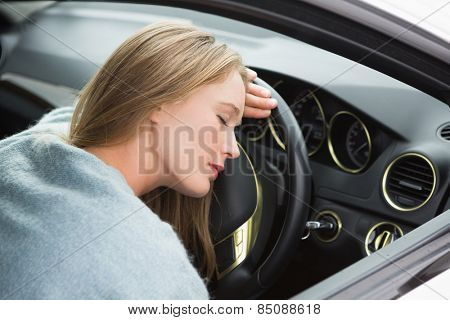 Tired woman asleep on steering wheel in her car