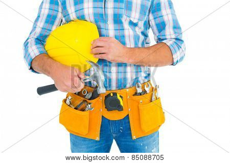 Midsection of manual worker wearing tool belt while holding hammer and helmet on white background