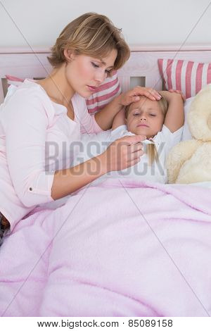 Mother taking the temperature of sick daughter at home in the bedroom