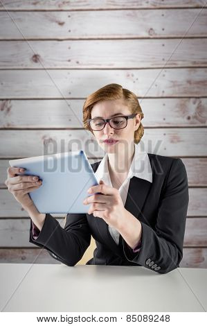 Redhead businesswoman using her tablet pc against wooden planks