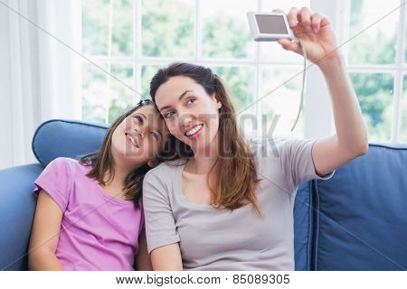 Mother and daughter taking a selfie at home in the living room