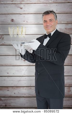 Smiling waiter holding tray with glasses with champagne against wooden planks