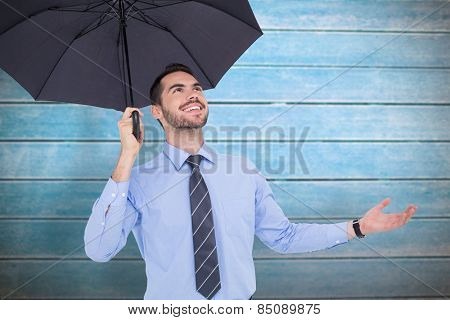 Happy businessman sheltering with a black umbrella against wooden planks