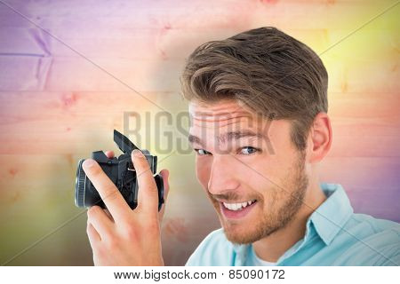 Handsome young man holding digital camera against yellow and purple planks