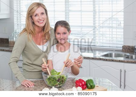 Mother and daughter preparing salad together at home in the kitchen