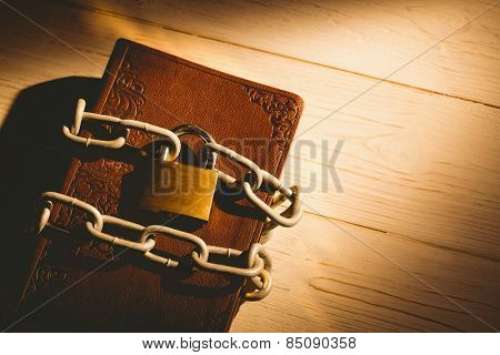 Open bible chained with lock on wooden table