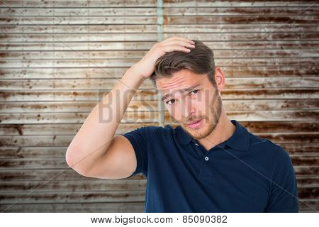 Handsome young man looking confused against wooden planks