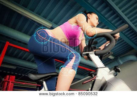 Determined young woman working out at spinning class against fitness interface
