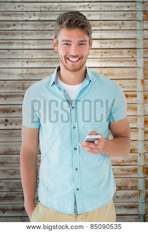 Handsome young man using his smartphone against faded pine wooden planks