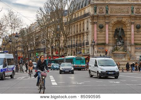 Typical Parisian street with cyclists, tourists and cars, France