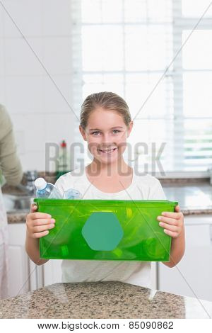 Happy little girl holding recycling box at home in the kitchen