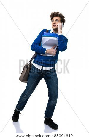 Full length portrait of a man walking on talking on the phone